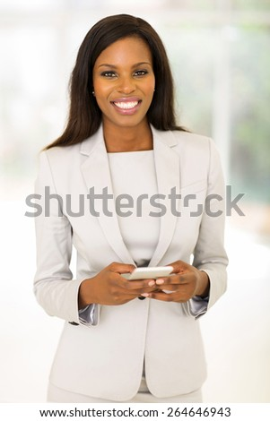 happy african businesswoman holding smart phone in office - stock photo