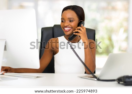 happy african businesswoman talking on landline phone and looking at computer - stock photo