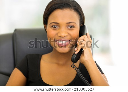 happy african businesswoman talking on phone in the office - stock photo