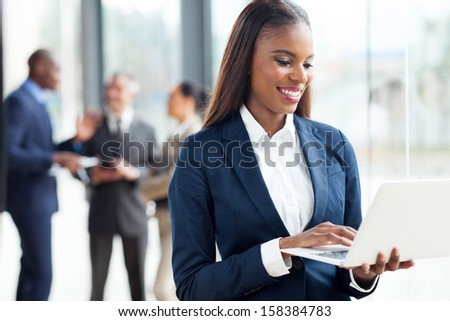 happy african businesswoman working on laptop computer - stock photo