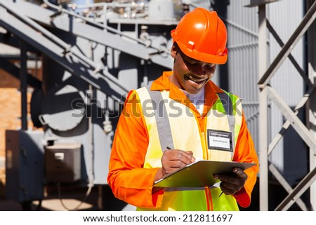 happy african electrician writing on clipboard in electric substation - stock photo