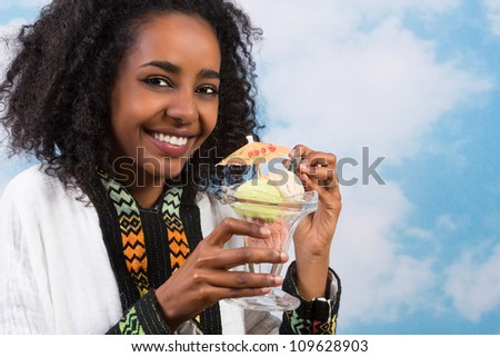 Happy African Ethiopian woman eating an icecream - stock photo
