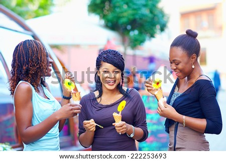 happy african friends eating ice cream outdoors - stock photo