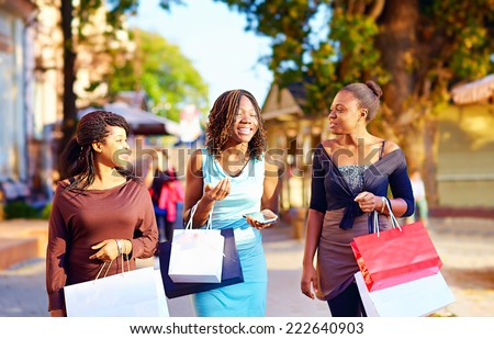 happy african girls walking the street with shopping bags - stock photo