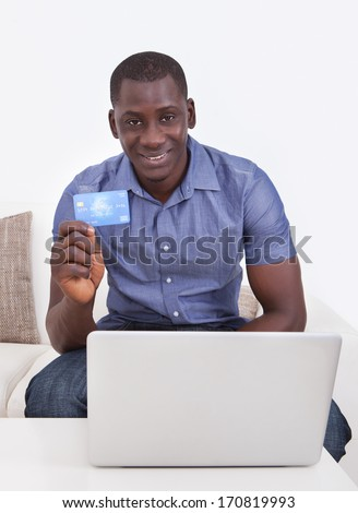 Happy African Man Holding Credit Card With Laptop On Table In Living Room - stock photo