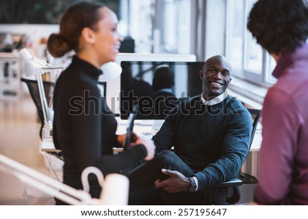 Happy african man sitting at desk with coworkers smiling. Young business executives during break. - stock photo