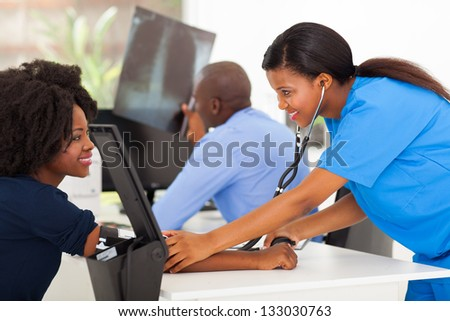 happy african medical nurse measuring patient's blood pressure in doctor's office - stock photo