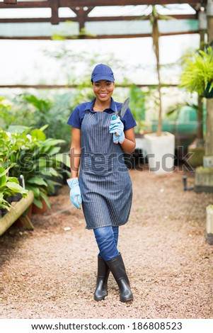 happy african nurser owner holding a shovel in greenhouse - stock photo