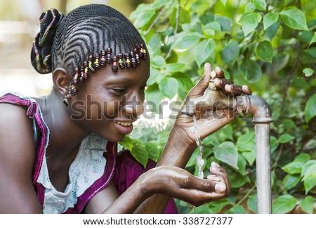 Happy African Schoolgirl Enjoying Clean Water from a Tap in Bamako, Mali - stock photo
