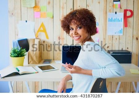 Happy african woman sitting by desk working from home office with laptop - stock photo