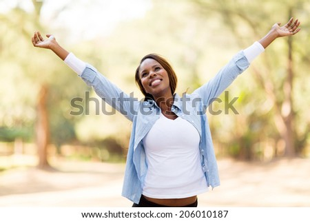 happy african woman with arms outstretched outdoors - stock photo