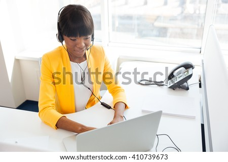 Happy afro american businesswoman in headset using laptop computer in office - stock photo