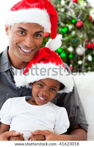 Happy Afro-American dad and daughter wearing a Christmas hat - stock photo
