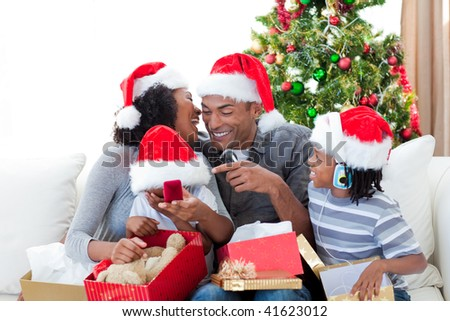 Happy Afro-American family having fun with Christmas presents at home - stock photo