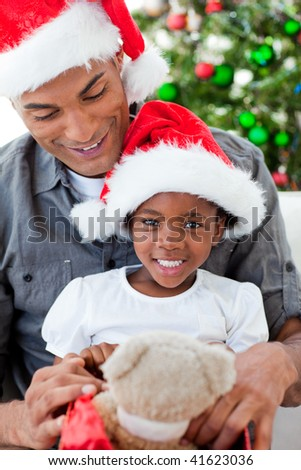 Happy Afro-American father and daughter playing with Christmas gifts - stock photo