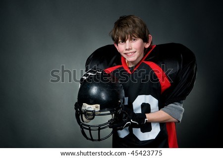 Happy american football player after victory, isolated on black - stock photo
