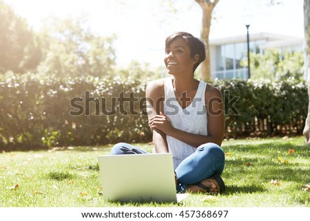 Happy and cheerful black female with short haircut sitting on the grass, smiling to her friends approaching her. Young African student using her notebook outdoor, resting after a hard day at college - stock photo