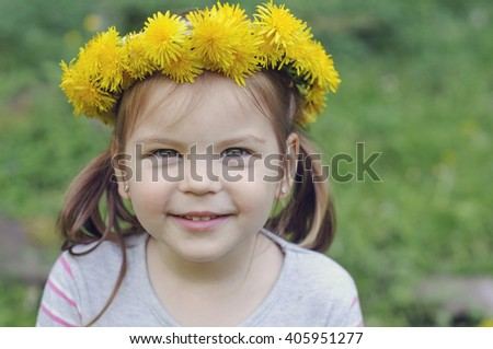 Happy and cheerful  child girl with a beautiful smile, with a wreath of dandelions. - stock photo
