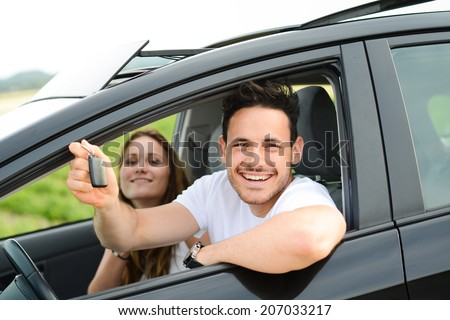 happy and cheerful young couple driving new car during holiday trip in summertime in countryside - stock photo