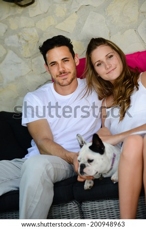 happy and cheerful young couple man woman with pet dog french bulldog sitting outdoor in sofa - stock photo