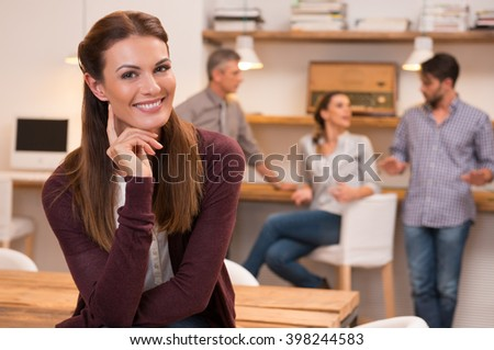 Happy and cheerful young woman looking at camera. Portrait of a beautiful smiling woman in office. Young casual woman sitting with hand near ear with colleagues in background.