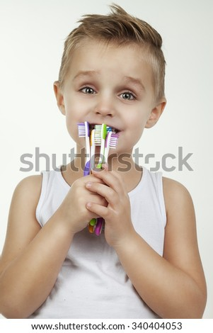 Happy and clean kid washing teeth wearing in white short shirt- isolated. Close up portrait of a little boy with color toothbrushes - stock photo