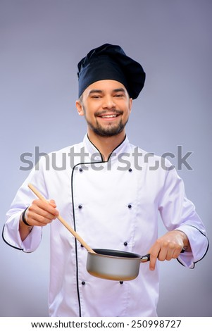 Happy and confident cook. Portrait of handsome cook holding a small pan and wooden spoon while standing over grey background with copy space - stock photo