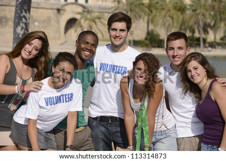 happy and diverse volunteer group smiling outdoors - stock photo