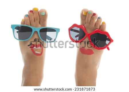 Happy and funny black summer feet with colorful nail polish and sunglasses - stock photo