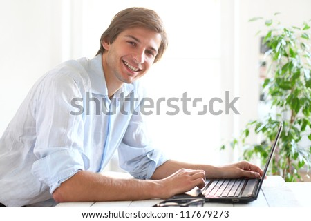 Happy and handsome man smiling and working on laptop - stock photo