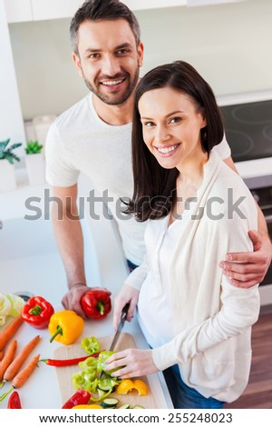 Happy and healthy couple. Top view of beautiful young couple bonding to each other and smiling while preparing food in the kitchen together  - stock photo