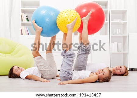 Happy and healthy family exercising at home using large gymnastic balls - stock photo