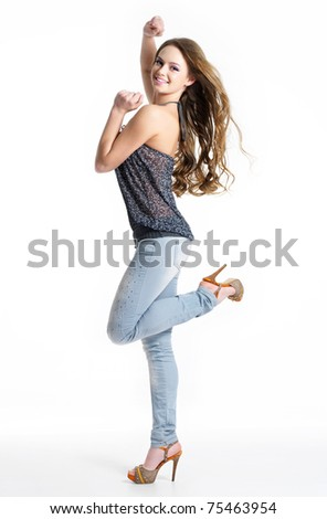 Happy and joy beautiful girl in fashion stylish jeans - isolated on white.  Fashion model posing at studio - stock photo