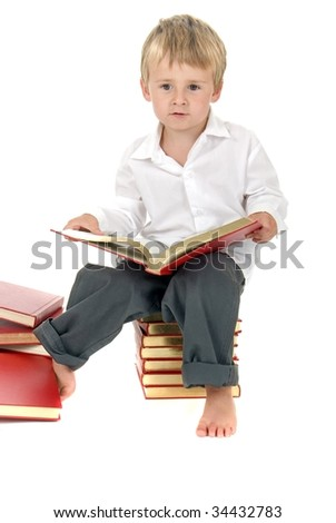 Happy and proud Boy sitting on stack of books reading - stock photo
