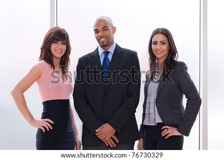 Happy and proud business team, three smiling young people. - stock photo