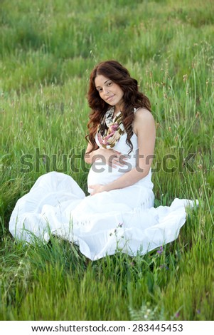 Happy and relaxed pregnant woman sitting on the grass - stock photo