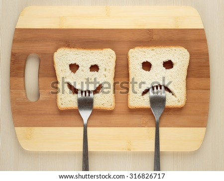 Happy and sad with a fork in her mouth on a cutting board - stock photo