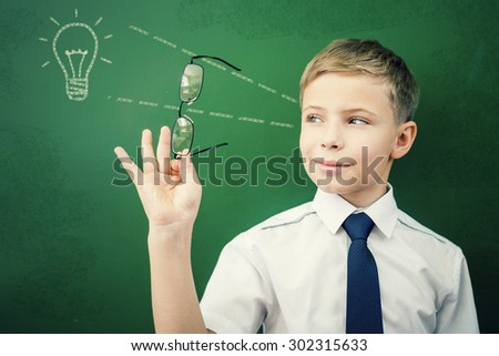 Happy and smart schoolboy standing near the blackboard and looking through glasses on new idea drawed a light bulb on the board! Concept of creative and educated student - stock photo