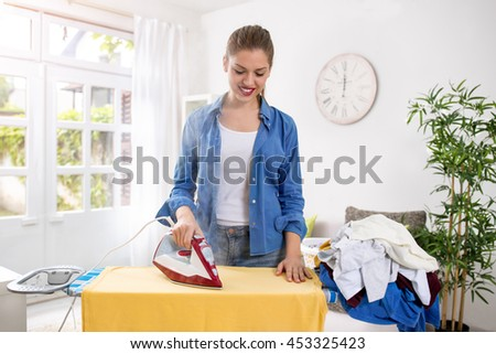 Happy and smiling young housewife enjoys in ironing her clothes - stock photo