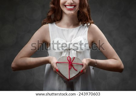 Happy and smiling young woman holding heart box with candies on grey background. Happy valentines gift concept - stock photo