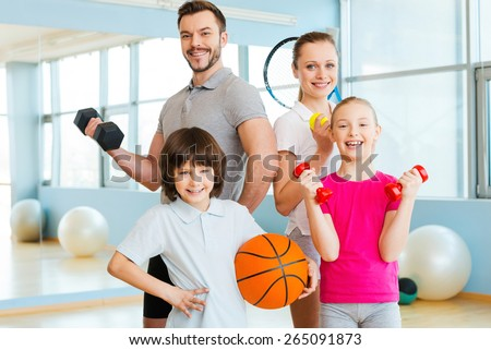 Happy and sporty. Happy family holding different sports equipment while standing close to each other in health club  - stock photo