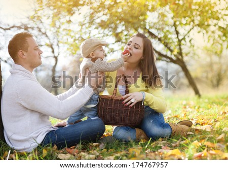 Happy and young family relaxing together in golden and colorful autum nature - stock photo