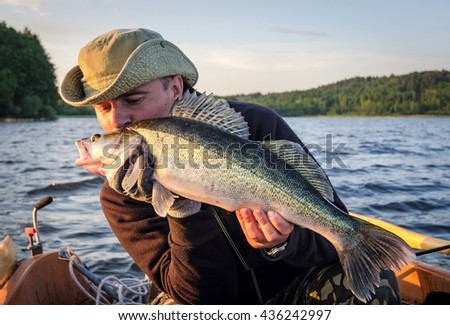 Happy angler kissing walleye fishing trophy - stock photo