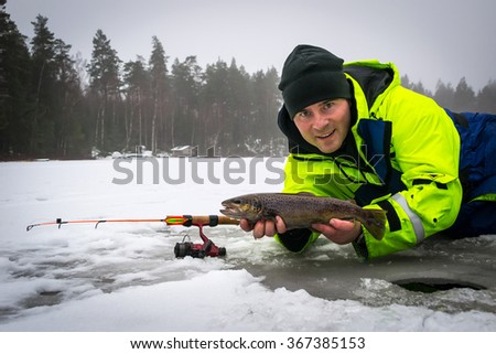 Happy angler with brown trout fishing trophy - stock photo