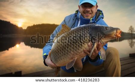 Happy angler with carp fishing trophy  - stock photo