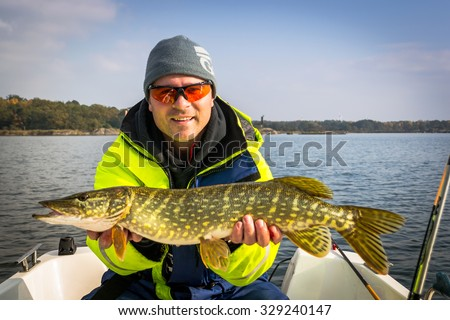 Happy angler with october's pike fishing trophy - stock photo