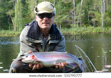 Happy angler with rainbow trout fishing trophy - stock photo