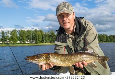 Happy angler with Swedish pike - stock photo