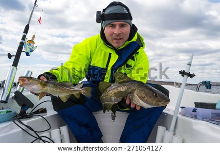 Happy angler with two Baltic cods - stock photo