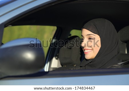 Happy arab saudi woman driving a car smiling with a headscarf - stock photo